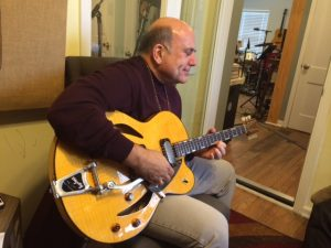 Playing a Versoul baritone guitar on the new album