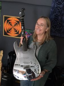 "Melissa showing a ""Mustang"" guitar given to her by the Ford Institute"